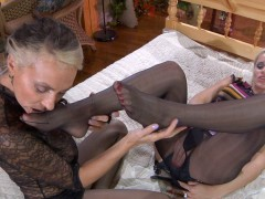 Sapphic blondes lick and sniff their nyloned feet before using a straponvideo